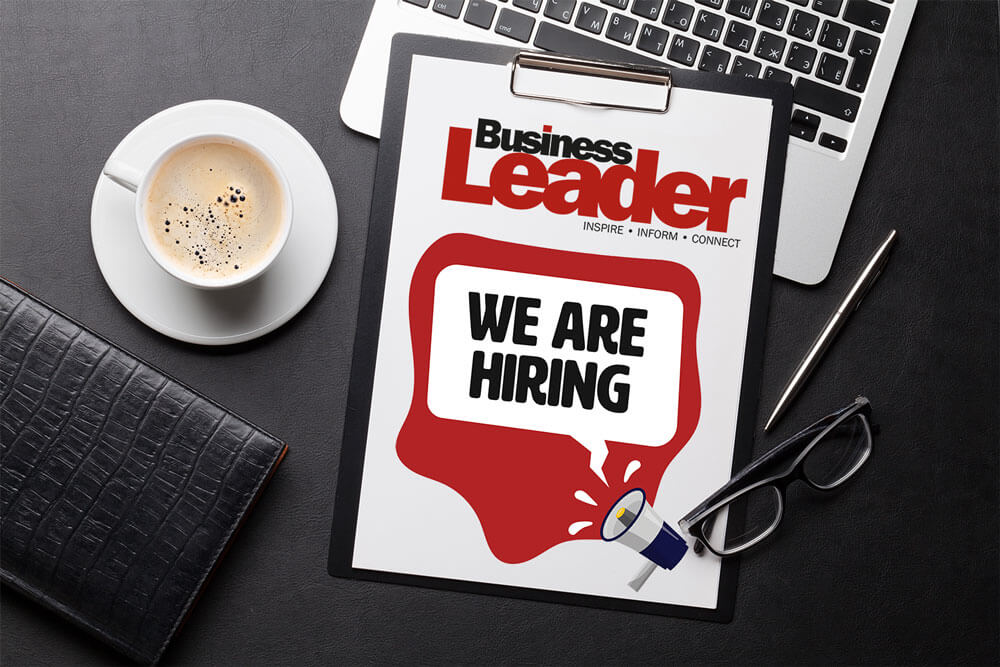 Business Leader hiring poster on a table with a laptop, coffee, glasses and notebook