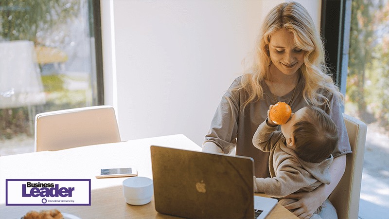 Single mother working on a laptop with a baby on her lap
